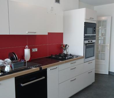 Cuisine noire et blanche avec crédence rouge et sol PVC ton gris