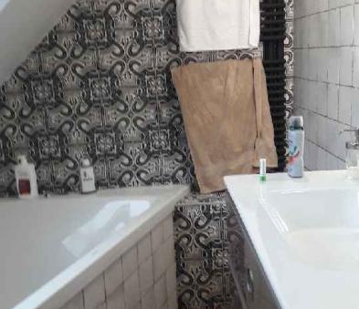 Faïence rétro vieilli et carreaux ciment, baignoire asymétrique et sèche serviette noir